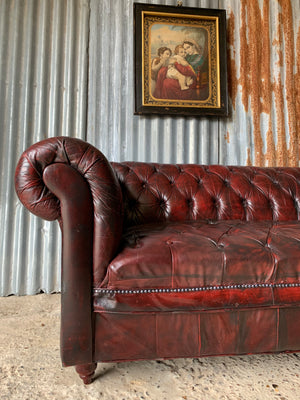 An oxblood three seater Chesterfield sofa with button back and seat