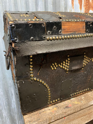 A black leather bound domed and studded wooden travel trunk