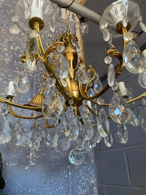 A heavily jewelled glass and brass 8 arm chandelier