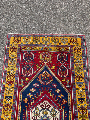 A rectangular Persian rug- red ground with yellow accents