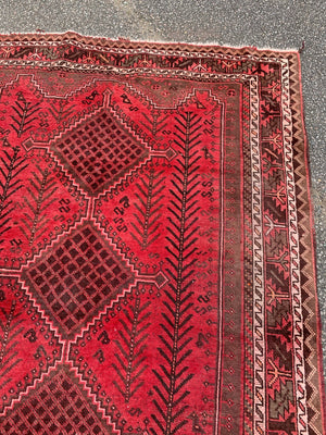 A large hand knotted Persian red ground rectangular rug