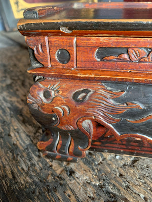 A carved wooden Chinese box with dragon motifs