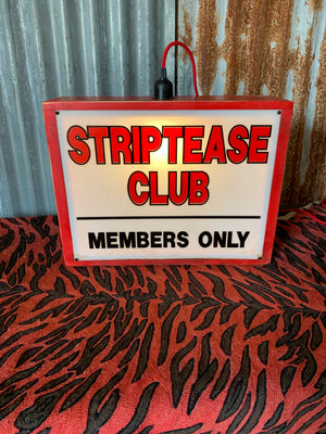 A striptease club illuminated light box advertising sign