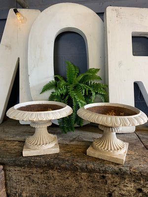 A pair of white cast iron tazza urns
