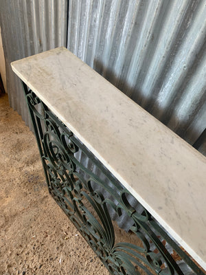 A tall cast iron strapwork console table with marble top