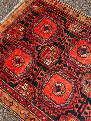 A large red ground Bokhara Persian rug with 'elephant foot' design