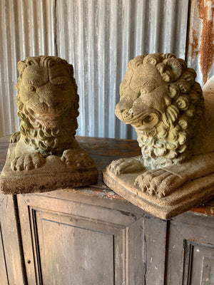 A pair of weathered cast stone lion statues