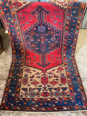 A long hand woven Persian red and blue ground rectangular rug