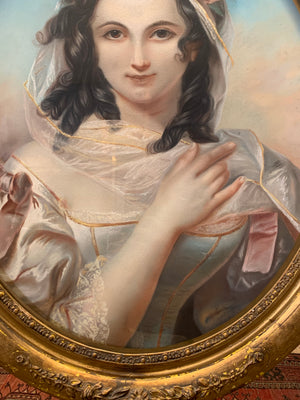 An early 19th Century chalk portrait of a lady in an ornate oval frame