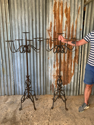 A Victorian pair of black cast iron floor standing church candelabra