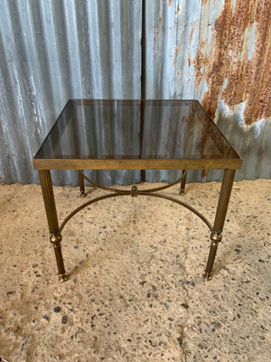 A Hollywood Regency square side table with smoked glass