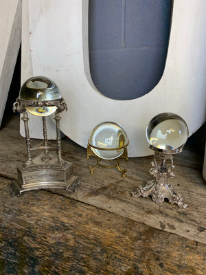 A large fortune teller's crystal ball on a silver plate swan stand
