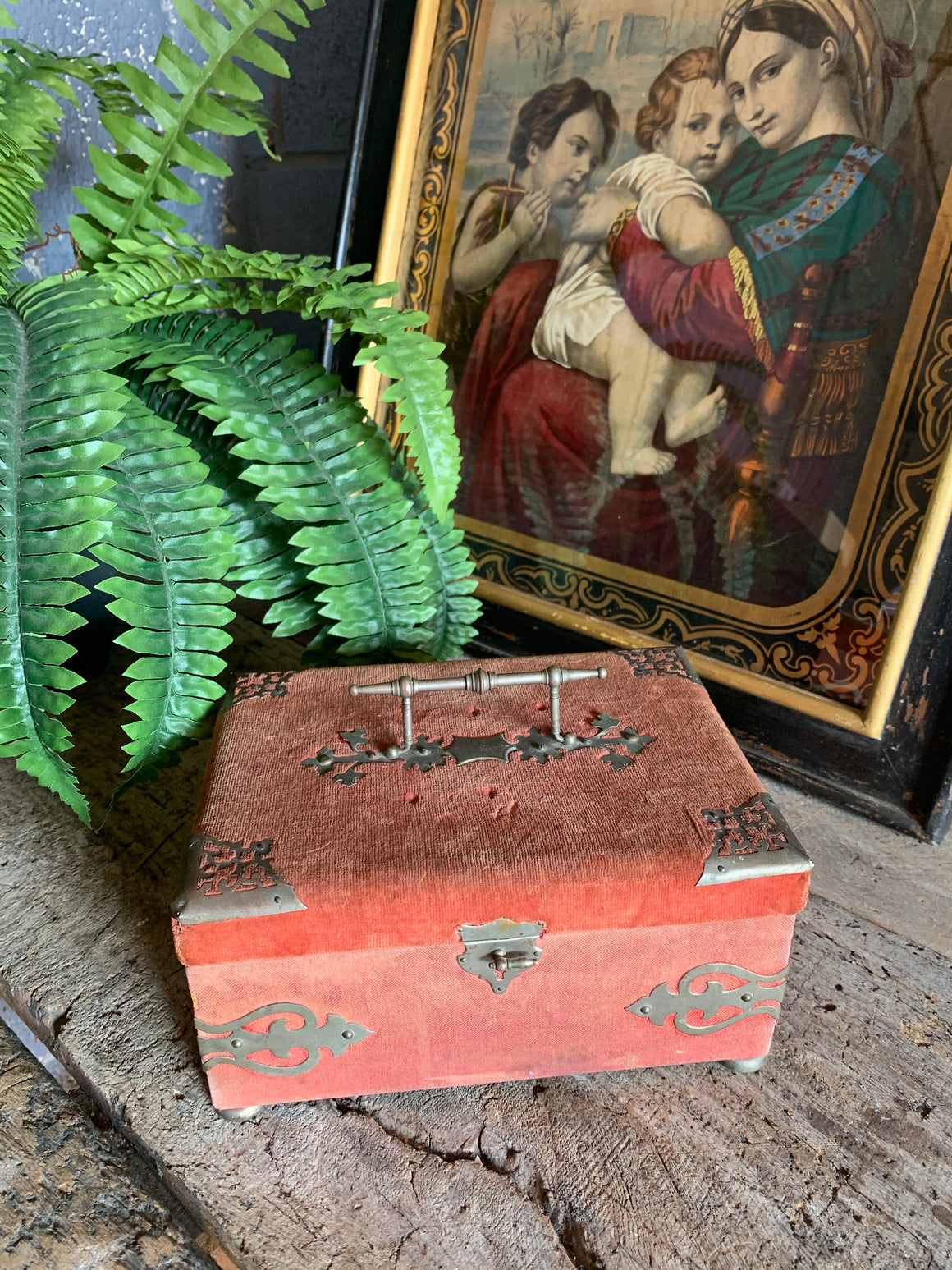 An ornate red velvet sewing box