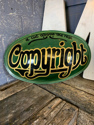 A convex 'Copyright: A Cut Above The Rest' trade advertising sign