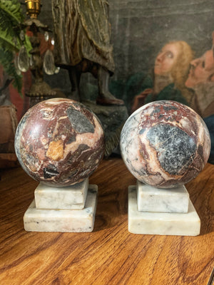 A pair of Grand Tour marble balls on stepped stands