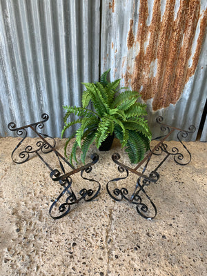 A weathered black wrought iron plant stand