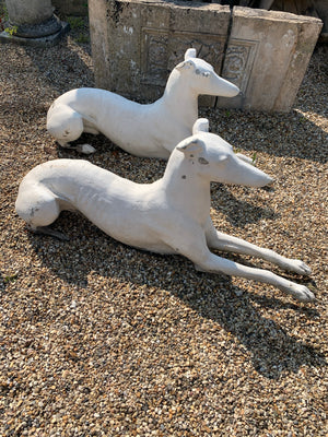 A pair of large white stone greyhound garden statues