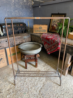 A vintage industrial copper pipe double clothing rack