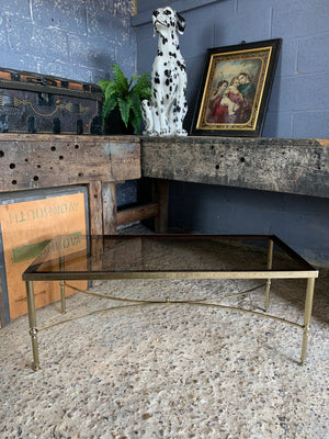 A Hollywood Regency rectangular coffee table with smoked glass