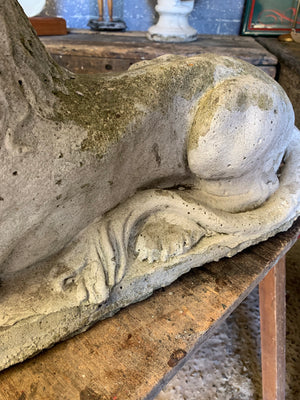 A pair of weathered cast stone recumbent lion statues