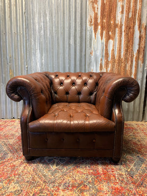 A brown Chesterfield armchair with button back and seat
