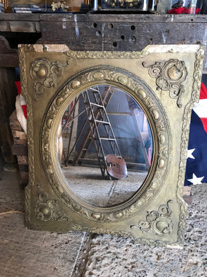 An ornate French rectangular gilt mirror with oval plate