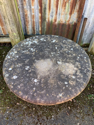 A large round weathered circular stone pedestal table