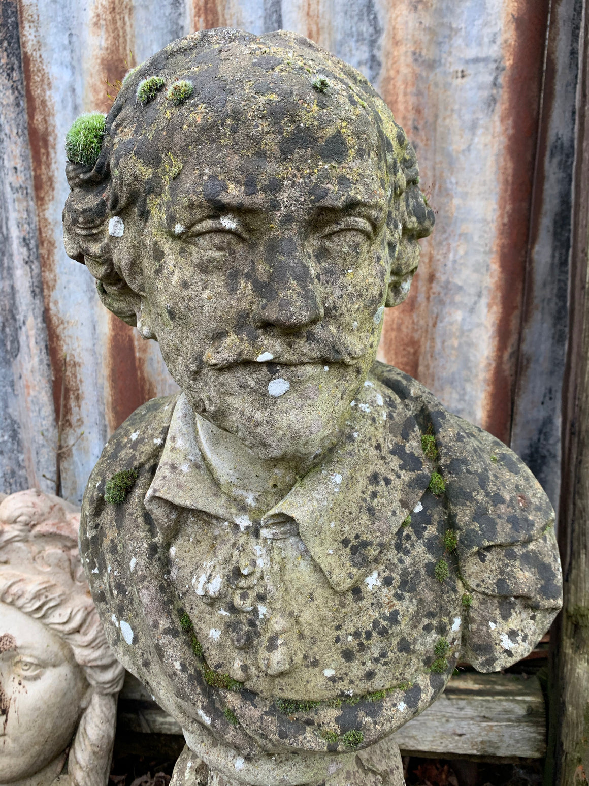 A weathered cast stone bust of Shakespeare on a pedestal column