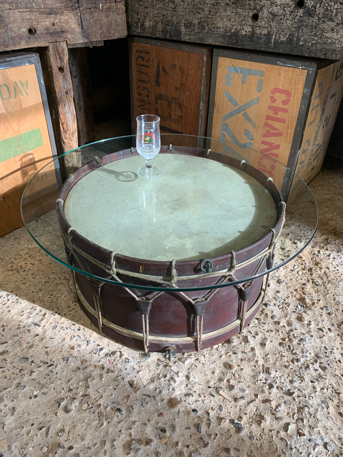 An antique wooden drum glass topped coffee table