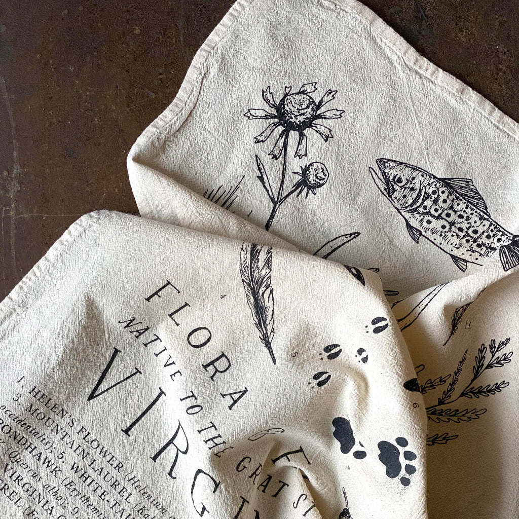A natural flour sack tea towel with Virginian wildlife printed in black ink on a dark wooden background.