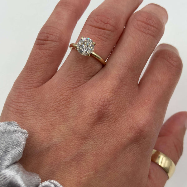 round moissanite engagement ring on the hand
