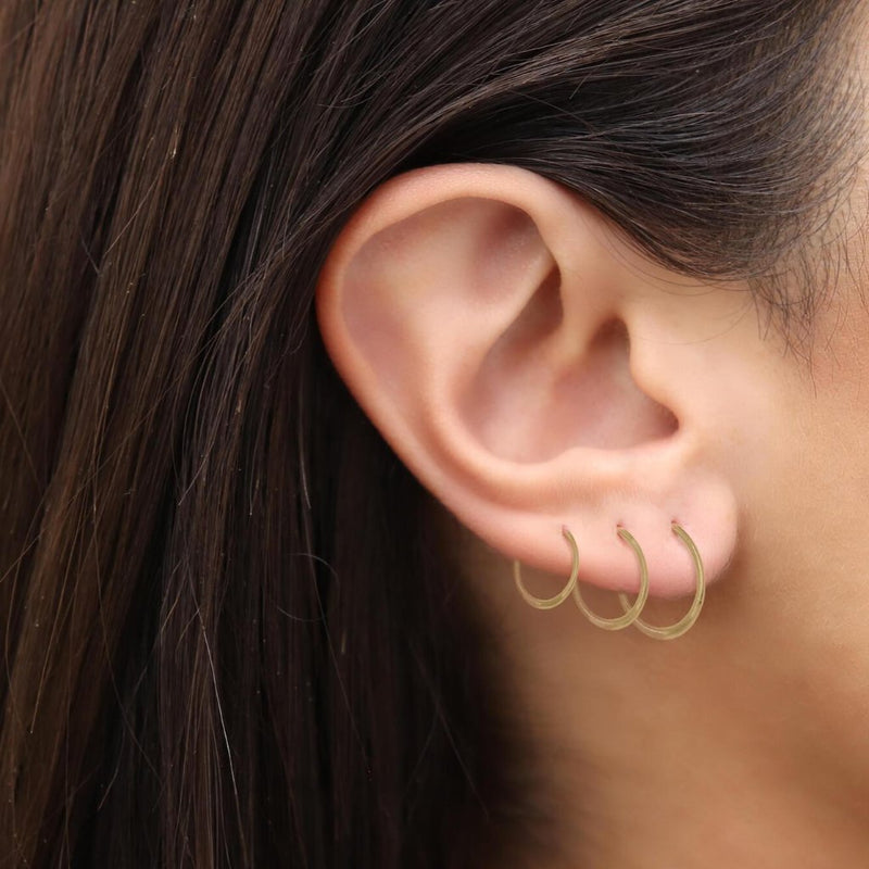 model wearing Gold Hoop Earrings 14K yellow gold