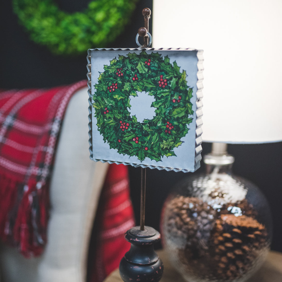 This little wall hanging features a pretty painting of a holly wreath. The border is created with a corrugated metal piece, adding to the rustic charm.