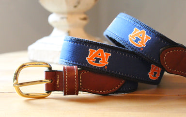 Auburn web belt with leather buckle. Blue ribbon with orange logo.