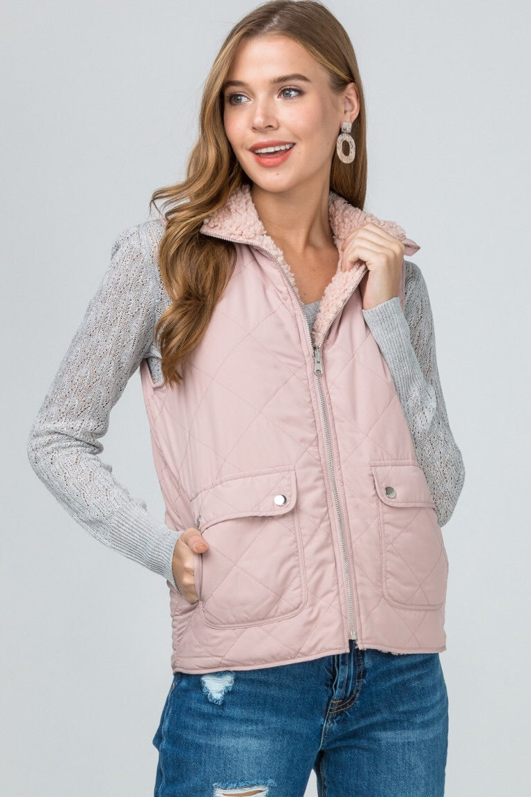 Reversible quilted/shearling vest featuring pocket detail at side. Non-sheer. Woven. Lightweight.