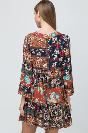 Patchwork print v-neck dress featuring bell sleeve detail. Lined. Non-sheer. Woven. Lightweight.