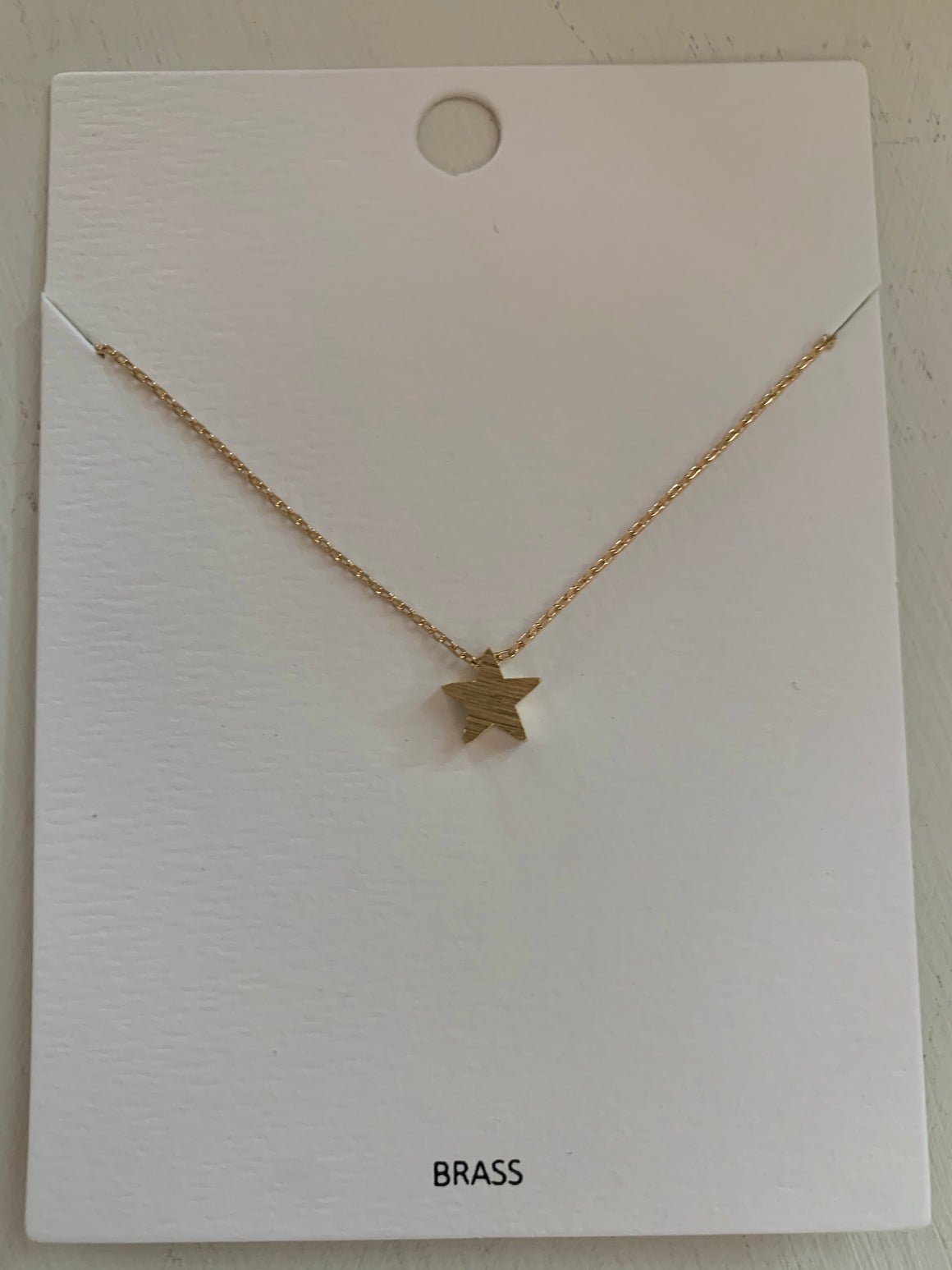 Star charm necklace with a satin gold finish.