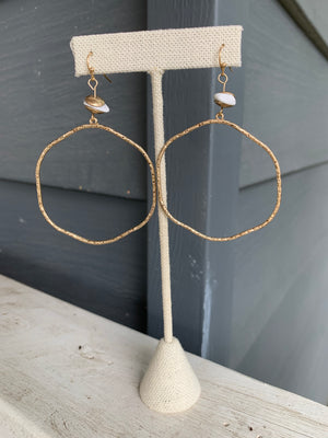Large gold hoop earrings with white stone and wire hook.