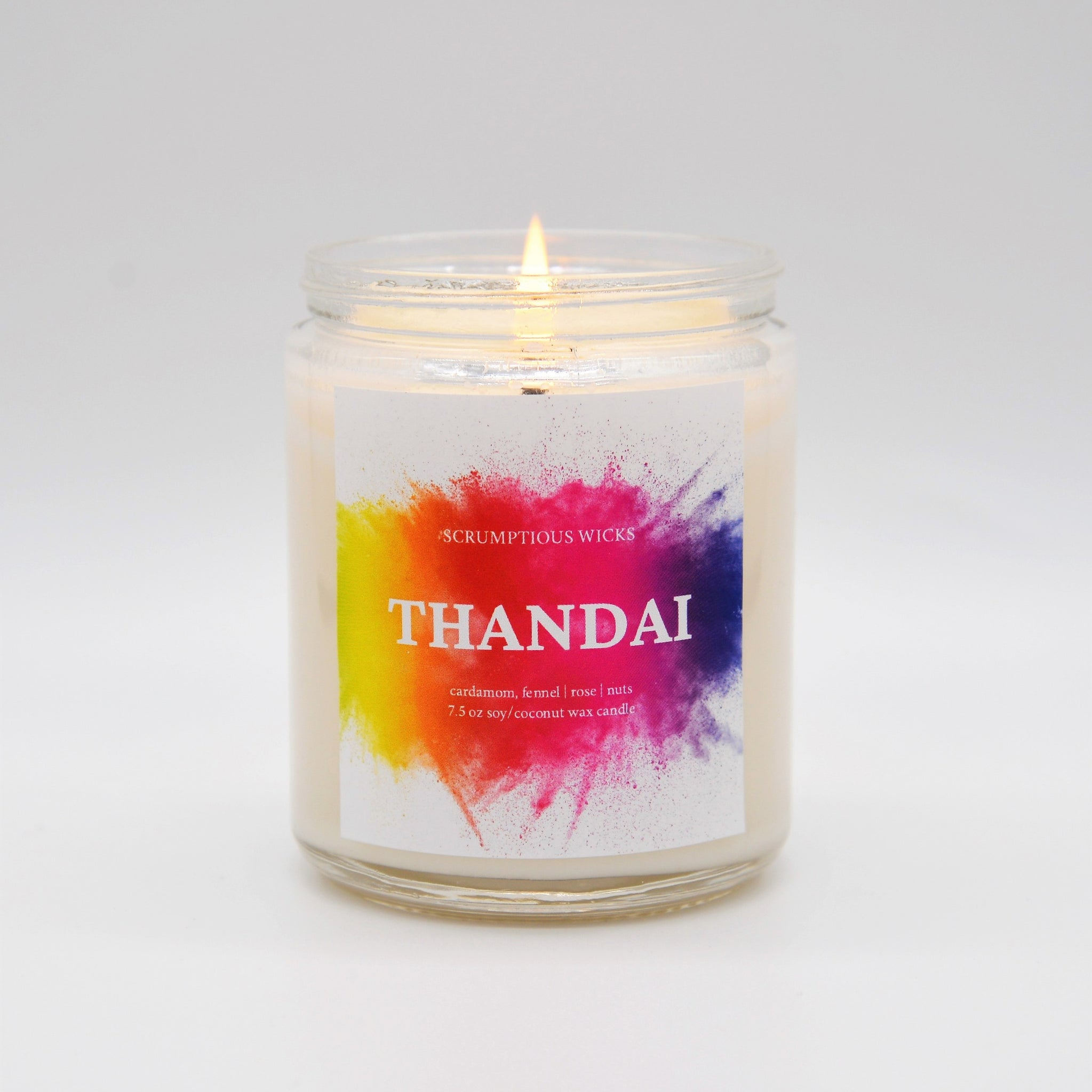Thandai scented candle in glass jar with lit flame and vibrant, colorful label