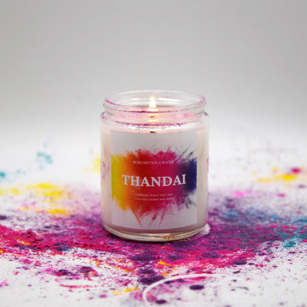 Thandai scented candle in glass jar with lit flame and vibrant, colorful label surrounded by colored powder for Holi, the festival of colors or festival of spring.