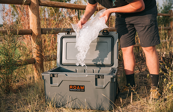 Man putting ice in a Rugged Cooler, a premium hard-sided cooler