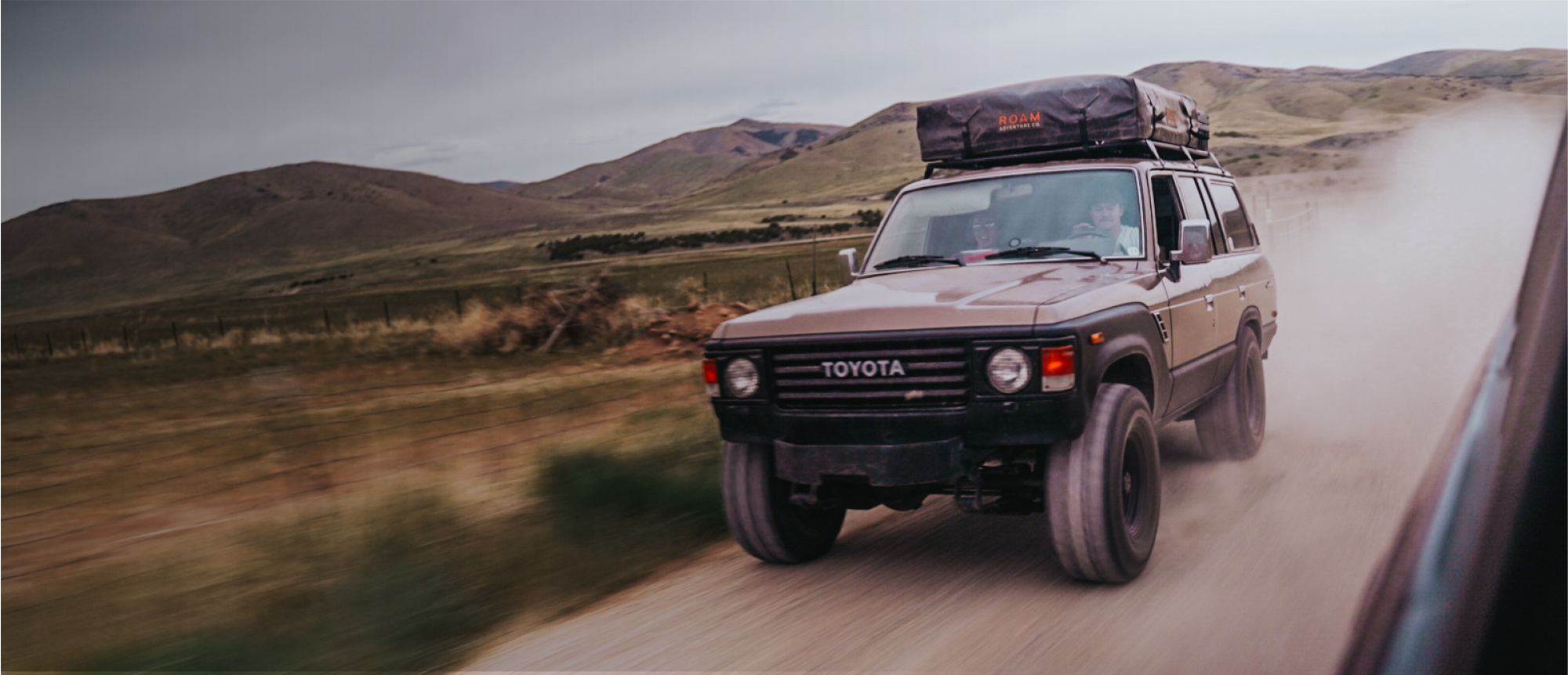 Toyota Land Cruiser with rooftop tent driving on dirt road