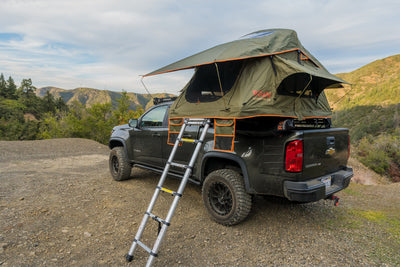 Vagabond Lite Rooftop Tent in Forest Green Hyper Orange with telescopic ladder shown on a truck