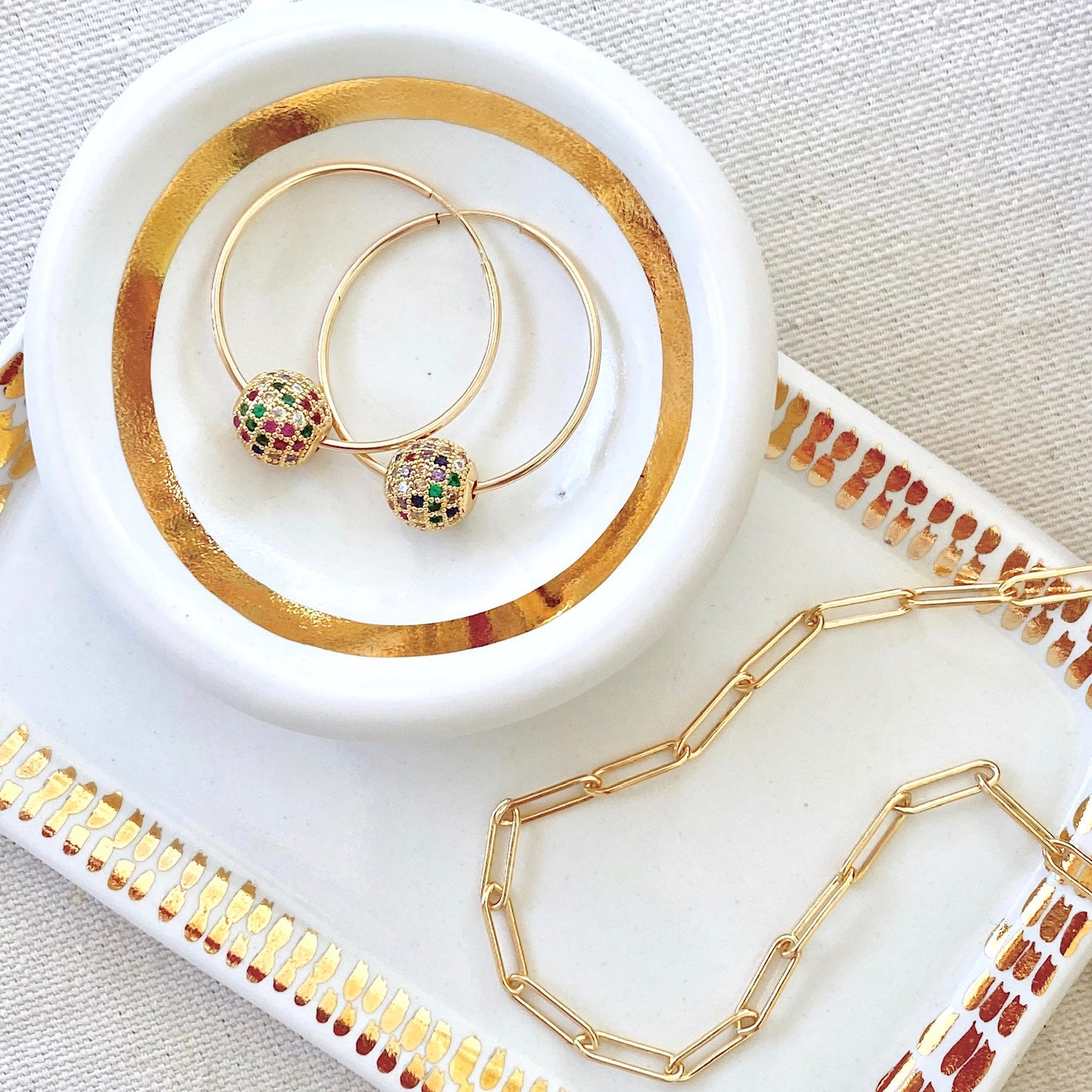 Hoop earrings with studded bead and paperclip necklace on the object enthusiast trinket dish and jewelry tray