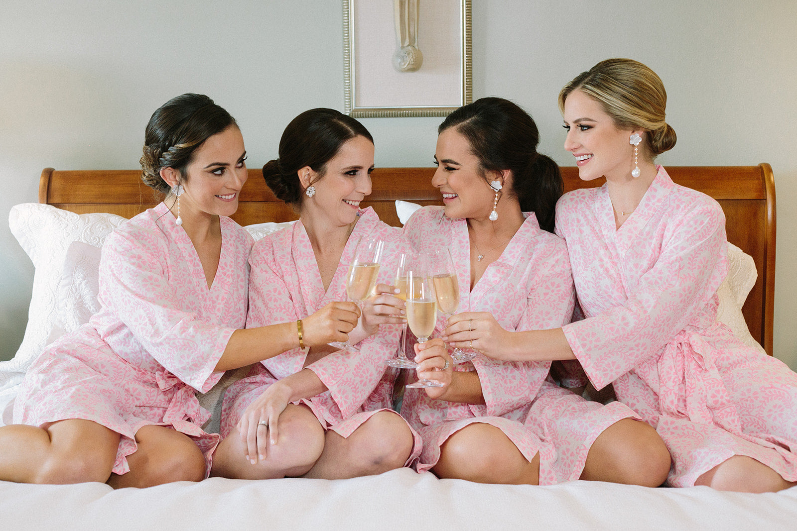 Bridesmaids and brides sitting on bed looking at each other