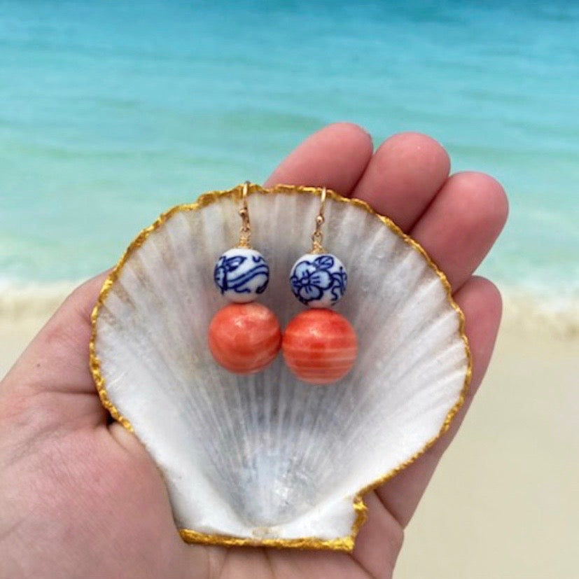 Coral and ceramic bead earrings on hook displayed in a seashell with ocean in background