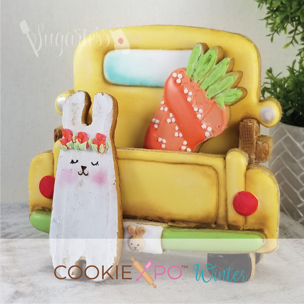 Sugartess custom cookie cutter set for Cookiexpo 2021 in shape of the back part of a classic pickup truck . 3D cookie truck is painted in yellow with green bumper and includes a tall bunny and carrot,