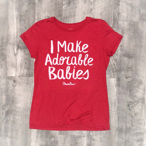 red womens t-shirt that says I make adorable babie, shirt is on a wood background