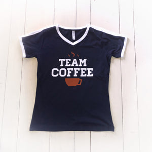 Blue athletic style shirt with white collar with a coffee much and steam with text Team Coffee