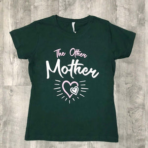 blueish green shirt that says the other mother, shirt is on a wood background